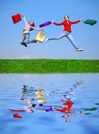 Girls jumping with bags against blue sky with reflection on water