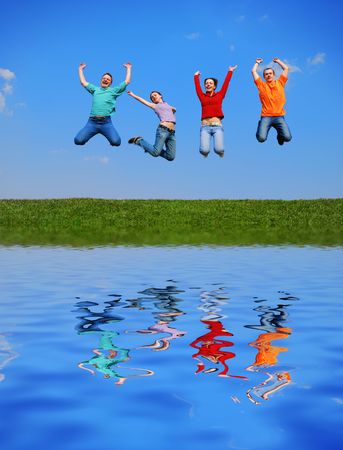 People jumping against blue sky with reflection on water photo