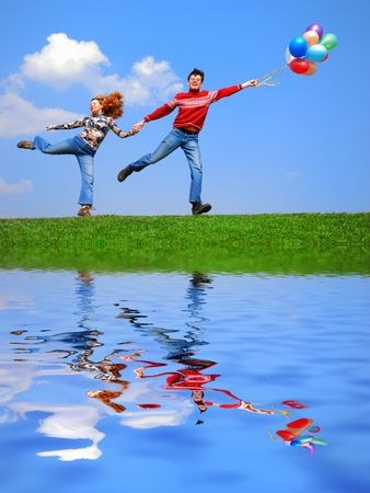 Couple with balloons against blue sky with reflection on water photo