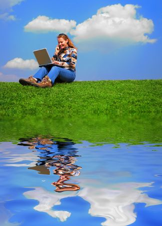 Girl with notebook sitting on grass against sky with reflection on water photo