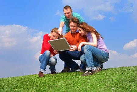 Group of people with notebook sitting on grass against sky                                     Stock Photo - 874212