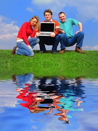 Group of people with notebook sitting on grass against sky with reflection on water Stock Photo - 874213