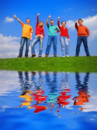 Group of people with thumbs up against blue sky with reflection on water photo