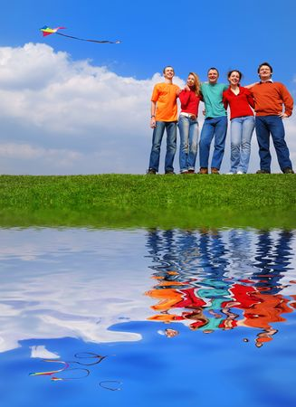 Group of people smiling against blue sky with reflection on water photo