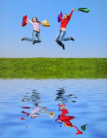 Girls jumping with bags against blue sky with reflection on water photo