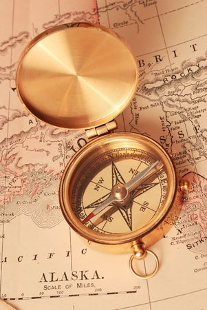 Antique brass compass over old Alaska map                                     photo