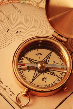 Antique brass compass over old USA map background