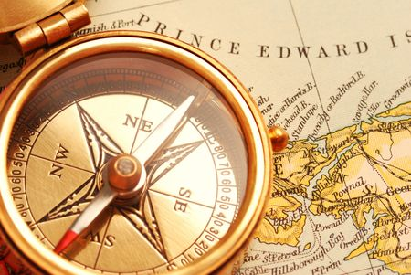 latitude: Antique brass compass over old Canadian map background