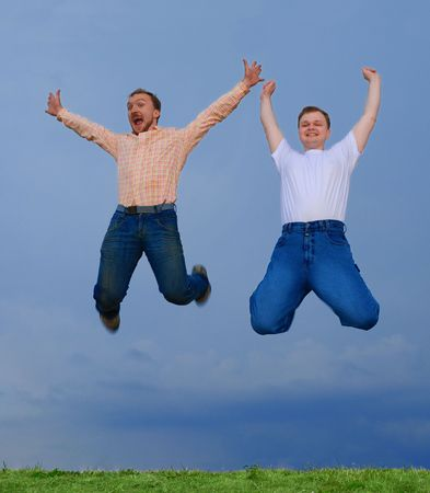 People jumping against cloudy dark sky Stock Photo - 1202041