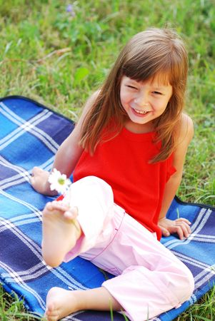 one girl only: Little cute girl with flower outdoors Stock Photo