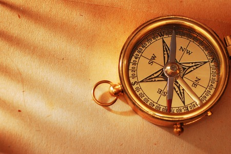 longitude: Antique brass compass over old map background