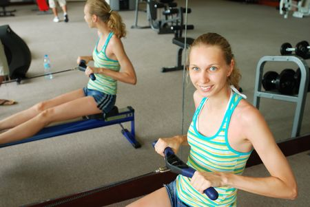 Girl in a fitness center. Row machine. photo