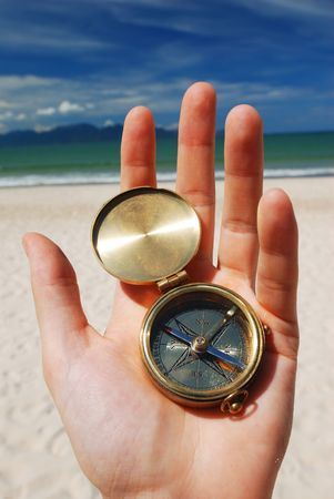 Compass in hand. Beach in background. photo