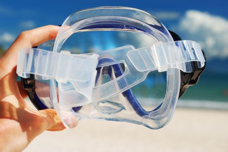 Snorkel equipment in hand against beach and sky Stock Photo - 2465567