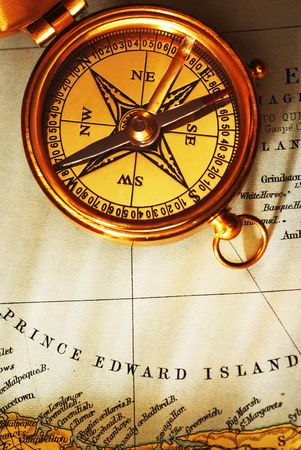 Antique brass compass over old Canadian map background photo
