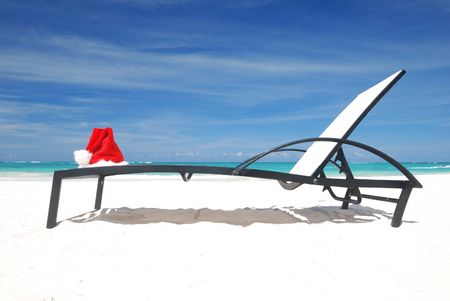 Santa's hat and chaise lounge on the beach Stock Photo - 3644083