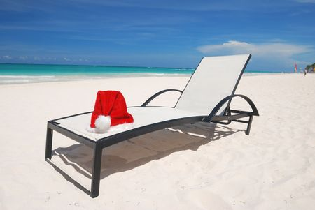 Santa's hat and chaise lounge on the beach Stock Photo - 3644091