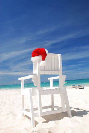 Santas hat and chair on the beach