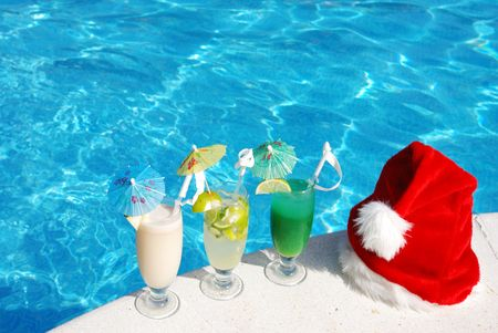 Santa hat and cocktails near the swimming pool Stock Photo