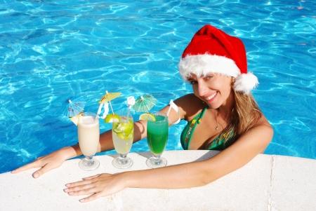 Girl in Santa hat near the swimming pool photo