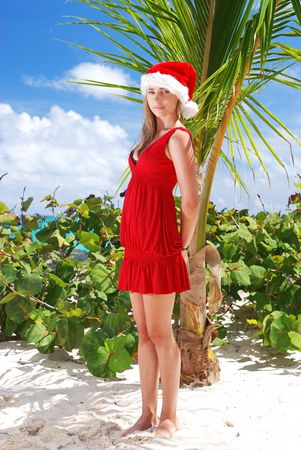 Woman on the beach in santas hat photo