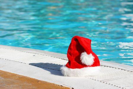 tropical christmas: Santa hat near the swimming pool