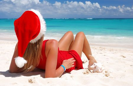 Woman on the beach in santas hat Stock Photo