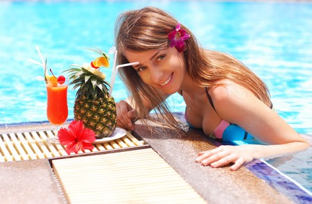 Girl in tropical pool with cocktail photo