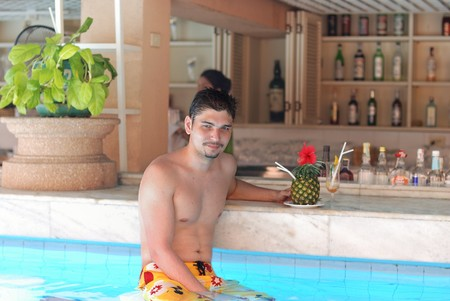 Man in tropical pool bar with cocktail photo