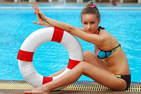 life saving: Girl near tropical pool with life saving buoy