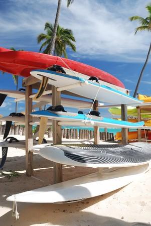 Rack of surf boards on caribbean beach photo