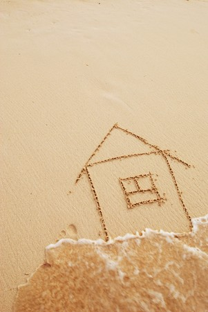 House drawn in sand. Wave blurred.