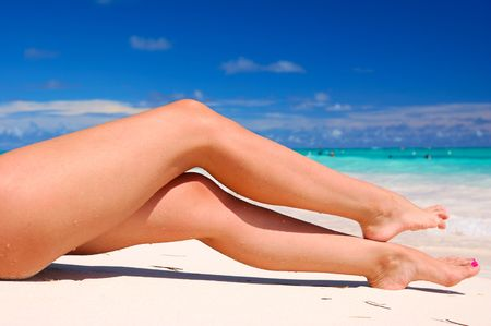 woman legs: Womens sexy legs on the beach Stock Photo