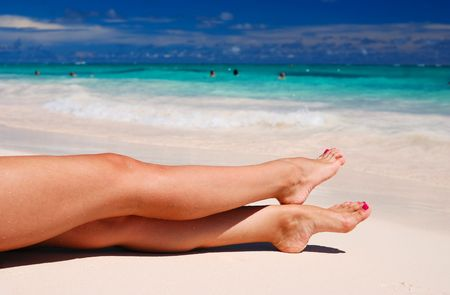 sexy legs: Womens sexy legs on the beach Stock Photo