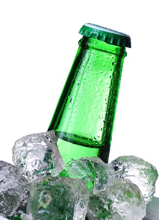 Green beer bottle in ice isolated on white photo