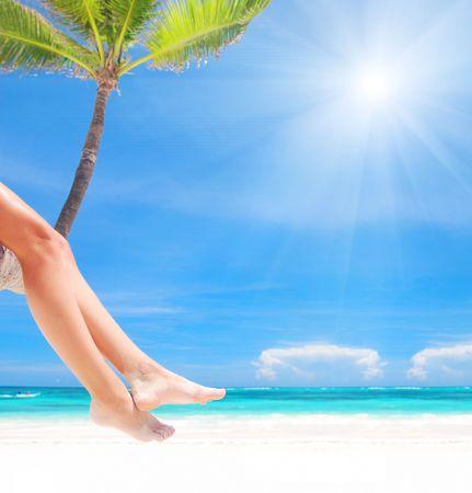 female legs: Woman on palm on caribbean beach