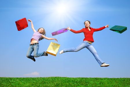 Girls jumping with bags against blue sky Stock Photo - 4974920
