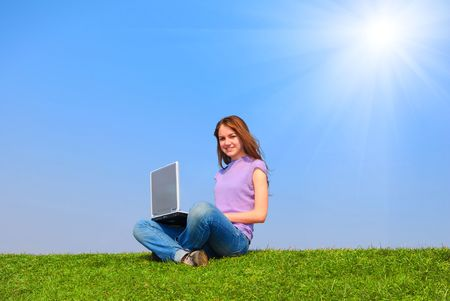 Girl with notebook sitting on grass against sky Stock Photo - 4993452