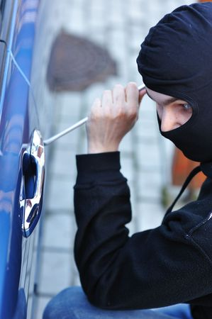 Young man in mask trying to steal a car photo