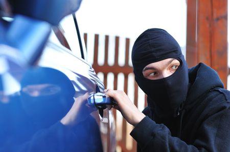 Hombre joven en máscara tratando de robar un coche