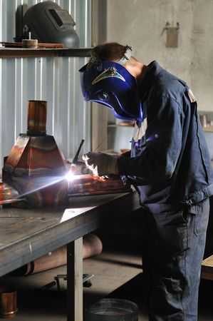 Welder working in protective mask photo