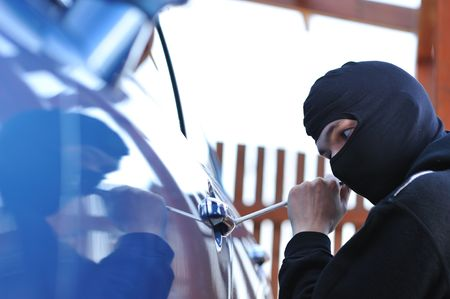 Young man in mask trying to steal a car Stock Photo - 5327960