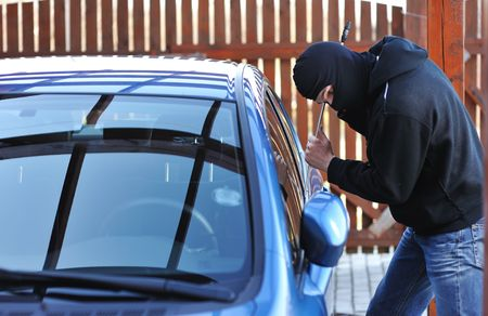 stealing: Young man in mask trying to steal a car