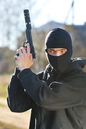 Gunman in black mask holding gun with silencer Stock Photo - 5474471