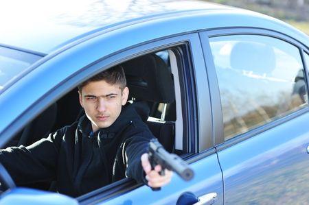 silencer: Gunman in car holding gun with silencer