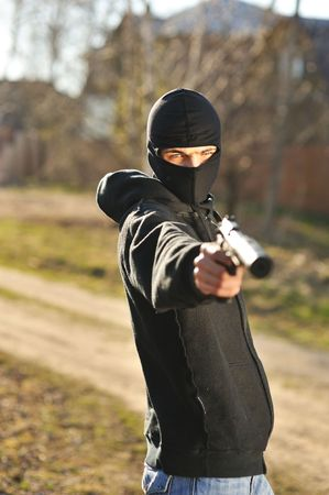one armed: Gunman in black mask holding gun with silencer