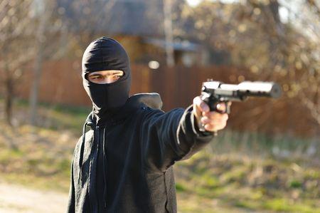Gunman in black mask holding gun with silencer photo