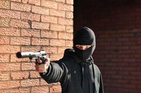 Gunman in black mask holding gun with silencer Stock Photo - 5494992