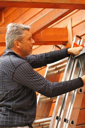 frontyard: Man on the ladder at backyard Stock Photo