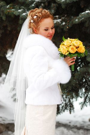 Bride holding bouquet of yellow roses photo